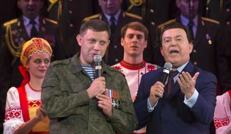 """FILE In this file photo taken on Monday, Oct. 27, 2014, Russian singer Iosif Kobzon, right, and Pro-Russian rebel leader Alexander Zakharchenko sing together during Iosif Kobzon's concert in the town of Donetsk, eastern Ukraine. Kobzon, an iconic Russian crooner and lawmaker dubbed """"the Soviet Sinatra"""" for his decades-long career, has died. He was 80. The Russian State Duma said in a statement that Kobzon died earlier on Thursday, Aug. 30, 2018. (AP Photo/Dmitry Lovetsky, File)"""