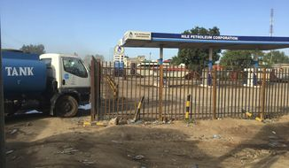 FILE - In this Sunday Oct. 1, 2017 file photo, a truck waits outside a closed petrol station of the Nile Petroleum Corporation in Juba, South Sudan. South Sudan says it will resume oil production in a key region in September 2018 to make up for more than $4 billion of revenue lost during years of fighting. (AP Photo/Sam Mednick, File)