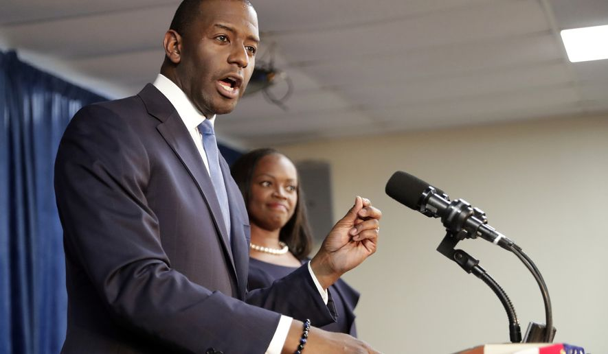 Florida Democratic gubernatorial candidate Andrew Gillum, left, speaks to supporters as his wife R. Jai Gillum listens during a Democratic Party rally Friday, Aug. 31, 2018, in Orlando, Fla. (AP Photo/John Raoux)