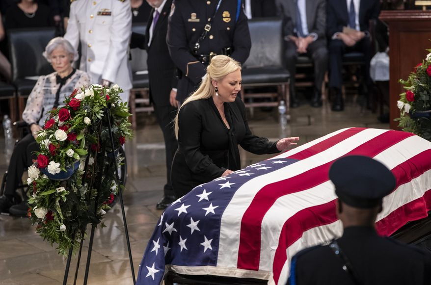 Meghan McCain reaches out to touch the flag-draped casket bearing the remains of her father, Sen. John McCain of Arizona, who lived and worked in Congress over four decades, during a farewell ceremony in the Capitol rotunda, Friday, Aug. 31, 2018, in Washington. His 106-year-old mother Roberta McCain is at far left. . (AP Photo/J. Scott Applewhite)