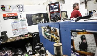 An employee works at his computer numerical control (CNC) milling machine at the Sheffer Corporation, a manufacturer of cylinders and actuators,, Friday, Aug. 31, 2018, in Blue Ash, Ohio. (AP Photo/John Minchillo)