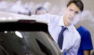Prime Minister Justin Trudeau uses a smoke wand during a demonstration of air flow over a car during a visit to the University of Ontario's Institute of Technology in Oshawa, Ontario, Friday, Aug. 31, 2018. (Chris Young/The Canadian Press via AP)
