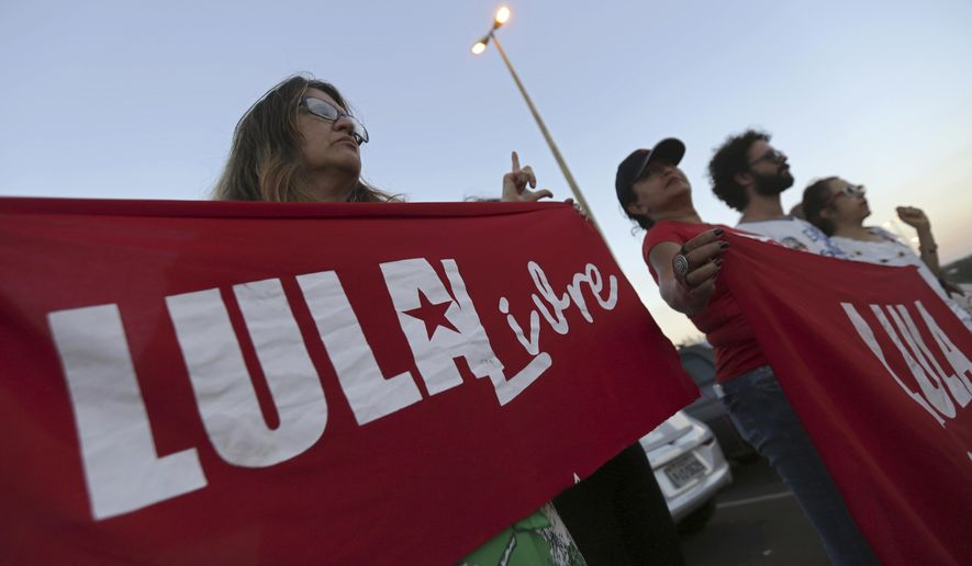 "Supporters of Brazil's Former President Luiz Inacio Lula da Silva, display banners with text written in Portuguese that read ""Free Lula"" during during a protest in front of the Superior Electoral Court, as the trial against the candidacy of the jailed former president continues, in Brasilia, Brazil, Friday, Aug. 31, 2018. Brazil's general elections will be held on October 7. (AP Photo/Eraldo Peres)"