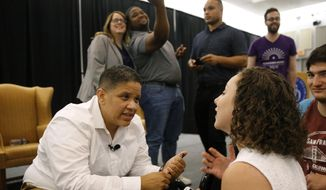 Kerri Evelyn Harris, left, Democratic candidate for U.S. Senate in Delaware, speaks with supporters following a town hall with New York congressional candidate Alexandria Ocasio-Cortez, Friday, Aug. 31, 2018, at the University of Delaware in Newark, Del. (AP Photo/Patrick Semansky)