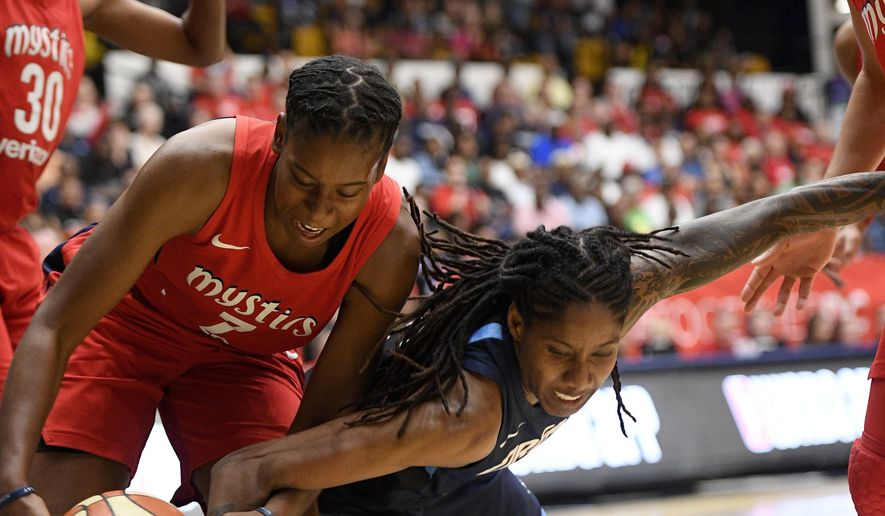Washington Mystics guard Ariel Atkins, left, battles for the ball against Atlanta Dream forward Jessica Breland, right, during the first half of Game 3 of a WNBA basketball playoffs semifinal Friday, Aug. 31, 2018, in Washington. (AP Photo/Nick Wass) ** FILE **