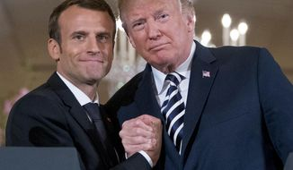 In this photo from Tuesday, April 24, 2018 , US President Donald Trump and French President Emmanuel Macron embrace at the conclusion of a news conference in the East Room of the White House in Washington.  (AP Photo/Andrew Harnik, File) **FILE**