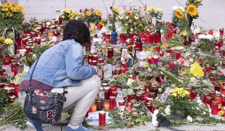 A woman knees in front of candles and flowers at the scene of an altercation in Chemnitz, Germany, Friday, Aug. 31, 2018. The protest late Monday, sparked by the killing of a 35-year-old German man in an altercation with migrants over the weekend, erupted into clashes between neo-Nazis and left-wing counter-protesters. (AP Photo/Jens Meyer)