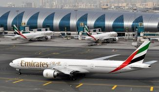 In this March 22, 2017, file photo, an Emirates plane taxis to a gate at Dubai International Airport in Dubai, United Arab Emirates. (AP Photo/Adam Schreck, File)