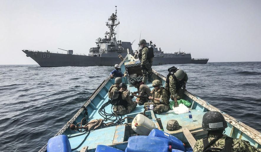 In this photo made available Thursday, Aug. 30, 2018, a team from the guided-missile destroyer USS Jason Dunham inspects a dhow while conducting maritime security operations. A U.S. military video released early Friday, Aug. 31, 2018, purported to show small ships in the Gulf of Aden smuggling weapons amid the ongoing war in Yemen, with officials saying they seized over 1,000 arms from the vessels. (U.S. Navy via AP)