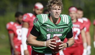 FILE - In this Aug. 9, 2018, file photo, North Carolina State quarterback Ryan Finley runs through a drill during an NCAA college football practice in Raleigh, N.C. Finley returned to school for his final season after flirting with entering the NFL draft and opens the year Saturday against James Madison. (AP Photo/Gerry Broome, File)