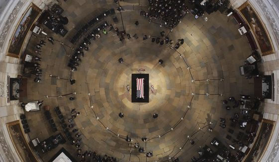 In this photo, Sen. John McCain, R-Ariz., lies in state in the U.S. Capitol Rotunda Friday, Aug. 31, 2018, in Washington. President George H.W. Bush will be honored similarly as he is to lie in state in the Rotunda from December 3-5, 2018. (Pool photo by Morry Gash via AP) **FILE**