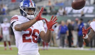 FILE - In this Aug. 24, 2018, file photo, New York Giants running back Saquon Barkley (26) warms up before the team's NFL preseason football game against the New York Jets in East Rutherford, N.J. Barkley, who has yet to take a snap in a real NFL game, has the best-selling jersey in the league. Barkley, the All-America running back from Penn State selected second overall in the draft by the Giants, is the leader according to DICK'S Sporting Goods Jersey Report. (AP Photo/Bill Kostroun, File)
