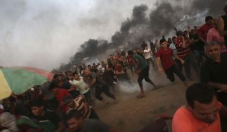 Protesters run to cover from teargas fired by Israeli troops, while others burn tires near fence of the Gaza Strip border with Israel, during a protest east of Gaza City, Friday, Aug. 31, 2018. Gaza's Health Ministry says Israeli gunfire wounded about 80 Palestinians at a weekly protest along the border with Israel. (AP Photo/Adel Hana)