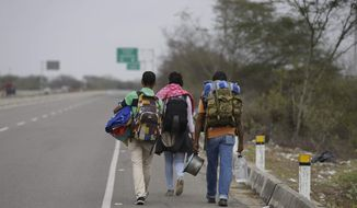 Venezuelan Omar Mujica, right, walks to Lima along the shoulder of the Pan-American Highway with other Venezuelan migrants after crossing the border from Ecuador into Peru, near Tumbes, Peru, Sunday, Aug. 26, 2018. Mujica, a car mechanic from Barquisimeto, said his car broke down before he started his trip, two weeks ago, and left it behind, unable to sell it. The U.N. estimates 2.3 million Venezuelans have fled since 2014 as the country with the world's largest proven oil reserves plummets into an economic crisis worse than the Great Depression. (AP Photo/Martin Mejia)