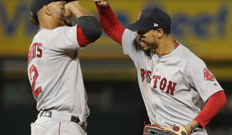 Boston Red Sox's Mookie Betts, right, and Xander Bogaerts celebrate the team's 9-4 win over the Chicago White Sox in a baseball game Thursday, Aug. 30, 2018, in Chicago. (AP Photo/Jim Young)