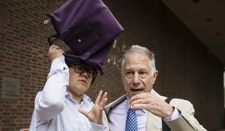 Yu Xue, left, accompanied by her attorney Peter Zeidenberg attempts to block her face with her bag as they exit the federal courthouse in Philadelphia, Friday, Aug. 31, 2018. Xue, a cancer researcher has pleaded guilty to conspiring to steal biopharmaceutical trade secrets from GlaxoSmithKline in what prosecutors said was a scheme to set up companies in China to market them. (AP Photo/Matt Rourke)