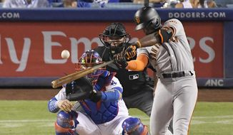FILE - In this Aug. 15, 2018, file photo, San Francisco Giants' Andrew McCutchen hits a three-run home run as Los Angeles Dodgers catcher Yasmani Grandal and home plate umpire Stu Scheurwater watch during the eighth inning of a baseball game in Los Angeles. The playoff-contending New York Yankees are close to completing a trade for San Francisco Giants outfielder Andrew McCutchen. A person familiar with the negotiations told The Associated Press on Thursday night, Aug. 30, 2018,  the Yankees would send infielder Abiatal Avelino and another minor leaguer to San Francisco for McCutchen. The person spoke on condition of anonymity because the deal wasn't finalized. (AP Photo/Mark J. Terrill, File)