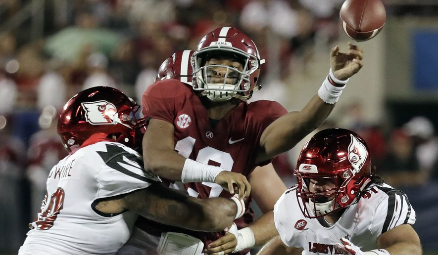 Alabama quarterback Tua Tagovailoa, center, manages to get off a pass as he is hit by Louisville defensive lineman Jared Goldwire, left, and defensive end Derek Dorsey (91) during the first half of an NCAA college football game, Saturday, Sept. 1, 2018, in Orlando, Fla. (AP Photo/John Raoux)