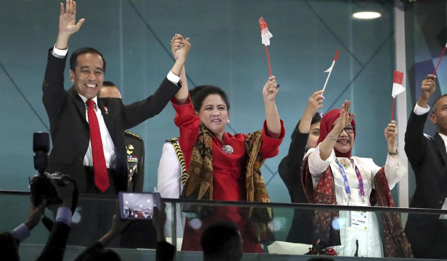 """FILE - In this Aug. 18, 2018, file photo, Indonesian President Joko Widodo, left, and his wife Iriana wave during the opening ceremony for the 18th Asian Games in the Gelora Bung Karno Stadium, Jakarta, Indonesia. Indonesia's hosting of the Asian Games and a record haul of gold medals has swelled national pride, providing a boost to the re-election campaign of President Joko """"Jokowi"""" Widodo. (AP Photo/Dita Alangakara, File)"""