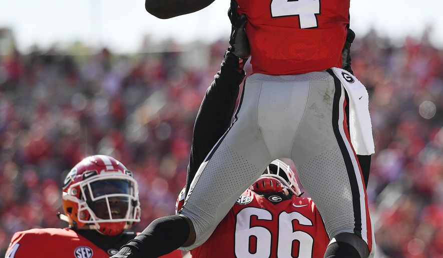 Georgia offensive lineman Solomon Kindley (66) lifts Georgia wide receiver Mecole Hardman (4) after Hardman's touchdown during the first half of an NCAA college football game, Saturday, Sept. 1, 2018, in Athens, Ga. (AP Photo/Mike Stewart)