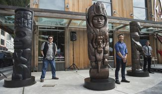 In this Aug. 26, 2018 photo, Tsimshian artist David R. Boxley, left, Tlingit artist Stephen Jackson, center, and Haida artist TJ Young, stand by their bronze house posts during an unveiling ceremony in front of the Walter Soboleff Center by Sealaska Heritage Institute in Juneau, Alaska. Each 8-foot-tall post at the corner of Front and Seward streets was carved respectively by a Tsimshian, Tlingit and Haida artist before casts were made and enduring, bronze versions were created in a Seattle foundry. (Michael Penn/The Juneau Empire via AP)