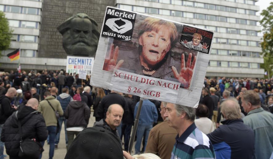 A protestor holds a poster with a photo of Angela Merkel referring reading she is guilty of incitement in Chemnitz, eastern Germany, Saturday, Sept. 1, 2018, after several nationalist groups called for marches protesting the killing of a German man last week, allegedly by migrants from Syria and Iraq. (AP Photo/Jens Meyer)