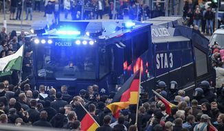 A police water cannon stands between far right demonstrators in Chemnitz, eastern Germany, Saturday, Sept. 1, 2018, after several nationalist groups called for marches protesting the killing of a German man last week, allegedly by migrants from Syria and Iraq (Ralf Hirschberger/dpa via AP)