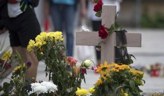A cross is decorated with flowers in Chemnitz, eastern Germany, Saturday, Sept. 1, 2018, at the site where 35-year-old man was stabbed the Sunday before. (Ralf Hirschberger/dpa via AP)