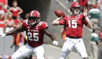 North Carolina State quarterback Ryan Finley passes while Reggie Gallaspy II (25) blocks during the first half an NCAA college football game against James Madison in Raleigh, N.C., Saturday, Sept. 1, 2018. (AP Photo/Gerry Broome)