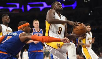 File-This Dec. 11, 2016, file photo shows Los Angeles Lakers forward Luol Deng (9), of South Sudan, drawing the foul from New York Knicks forward Carmelo Anthony (7) as he drives to the basket during the second half of an NBA basketball game in Los Angeles. The Lakers have waived Deng two years after signing him to a four-year, $72 million free-agent contract. The Lakers announced the move Saturday, Sept. 1, 2018, the first day in which the final season of Deng's mammoth deal could be stretched over a three-season span of the Lakers' salary cap limit.  (AP Photo/Gus Ruelas, File)