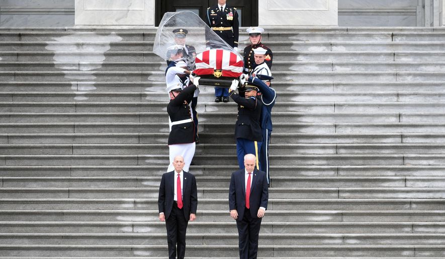 A plastic cover blows off in the wind as the flag-draped casket of Sen. John McCain, R-Ariz., is carried down the steps of the U.S. Capitol in Washington, Saturday, Sept. 1, 2018, in Washington, for a departure to the Washington National Cathedral for a memorial service. (Marvin Joseph/The Washington Post via AP, Pool)