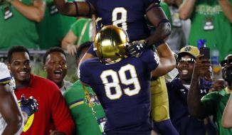 Notre Dame's Jafar Armstrong (8) celebrates his 4-yard touchdown run with Brock Wright (89) in the first half of an NCAA football game against Michigan in South Bend, Ind., Saturday, Sept. 1, 2018. (AP Photo/Paul Sancya)