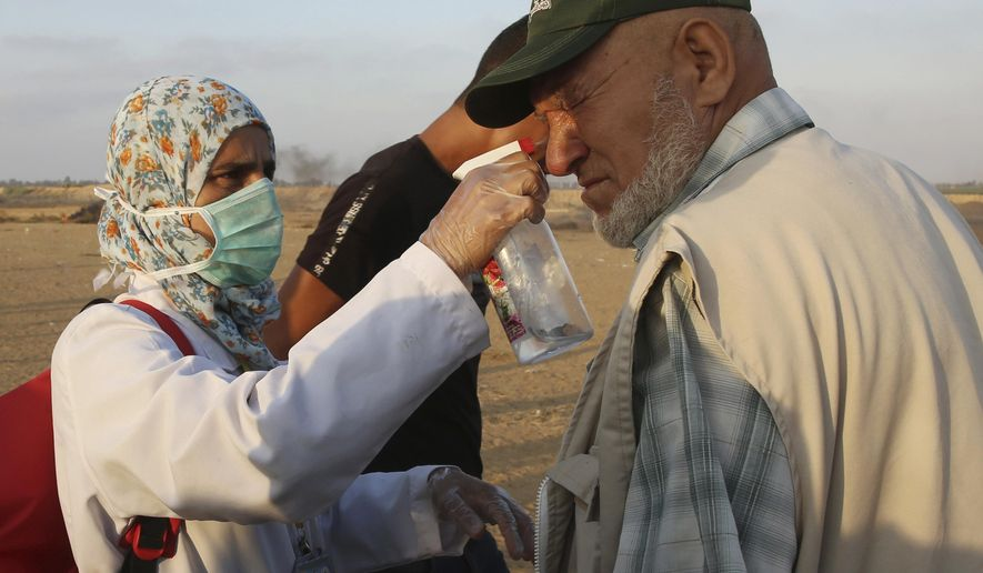 In this Friday, Aug. 24, 2018 photo, Palestinian paramedic Asmaa Qudih sprays a homemade anti teargas liquid on a man near the fence of the Gaza Strip border with Israel, during a protest east of Khan Younis, southern Gaza Strip. Treating the wounded has become dangerous mission for Gaza's emergency workers. (AP Photo/Adel Hana)