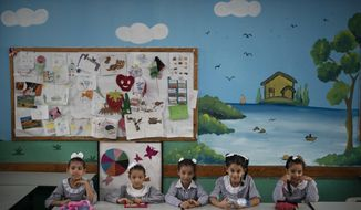 "File - In this Wednesday, Aug. 29, 2018 file photo, girls sit inside a classroom at an UNRWA school during the first day of a new school year in Gaza City. A spokesman for the Palestinian president says the American decision to cut funding for the U.N. agency aiding Palestinian refugees is ""an attack on the rights of the Palestinian people."" The U.S. supplies nearly 30 percent of the total budget of the U.N. Relief and Works Agency, or UNRWA, and had been demanding it carry out significant reforms. The decision cuts nearly $300 million of planned support. (AP Photo/Felipe Dana, File)"