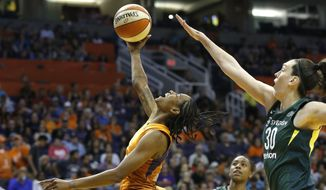 Phoenix Mercury guard Yvonne Turner, left, gets off a shot in front of Seattle Storm forward Breanna Stewart (30) as Storm guard Jewell Loyd, rear, watches during the second half of Game 3 of a WNBA basketball playoffs semifinal Friday, Aug. 31, 2018, in Phoenix. The Mercury defeated the Storm 86-66. (AP Photo/Ross D. Franklin)