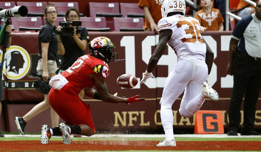 Maryland wide receiver Taivon Jacobs, left, catches a touchdown pass in front of Texas defensive back Kobe Boyce in the first half of an NCAA college football game, Saturday, Sept. 1, 2018, in Landover, Md. (AP Photo/Patrick Semansky) **FILE**