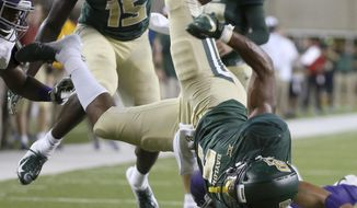 Baylor running back John Lovett (7) is upended by Abilene Christian safety Erik Huhn (4) during the first half of an NCAA college football game Saturday, Sept. 1, 2018, in Waco, Texas. (Jerry Larson/Waco Tribune Herald via AP)