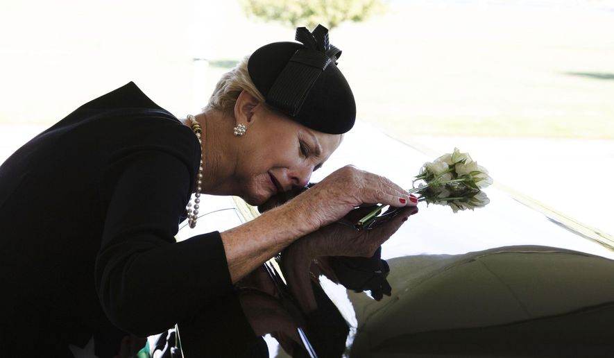 In this photo provided by the family of John McCain, Cindy McCain lays her head on the casket of Sen. John McCain, R-Ariz., during a burial service at the cemetery at the United States Naval Academy in Annapolis, Md., on Sunday, Sept. 2, 2018. (David Hume Kennerly/McCain Family via AP)