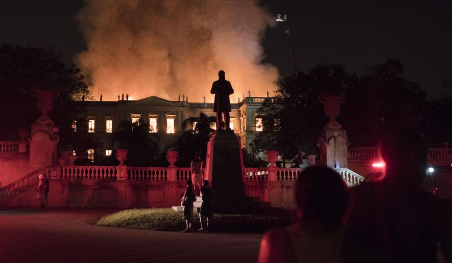 People watch as flames engulf the 200-year-old National Museum of Brazil, in Rio de Janeiro, Brazil, Sunday, Sept. 2, 2018. According to its website, the museum has thousands of items related to the history of Brazil and other countries. The museum is part of the Federal University of Rio de Janeiro (AP Photo/Leo Correa)