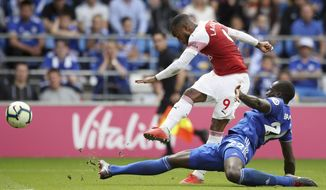 Arsenal's Alexandre Lacazette, top, scores his side's third goal during a Premier League soccer match between Cardiff City and Arsenal, at the Cardiff City Stadium, Wales, Sunday, Sept. 2, 2018. (Nick Potts/PA via AP)