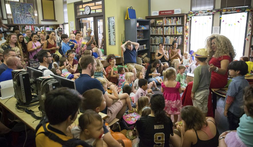 Vanessa Carr , right, reads to children during Drag Queen Story Time at the Alvar Library in New Orleans on Saturday, Aug. 25, 2018. Children and parents and caregivers packed into the library to hear drag queens Blazen Haven and Carr read stories and sing songs during the event. (Scott Threlkeld/The Advocate via AP) **FILE**