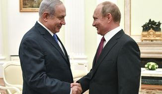 FILE - In this July 11, 2018, file photo, Russian President Vladimir Putin, right, shakes hands with Israeli Prime Minister Benjamin Netanyahu during their meeting at the Kremlin in Moscow. Netanyahu is one of the few world leaders to enjoy warm ties with both the Russian and American presidents. Netanyahu has made frequent visits to Moscow in recent years to meet with Putin and coordinate Israeli operations in neighboring Syria with those of Russian forces. (Yuri Kadobnov/ Pool Photo via AP, File)
