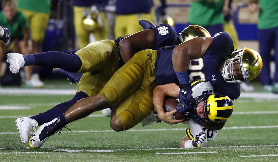 Notre Dame defensive lineman Jerry Tillery (99) tackles Michigan quarterback Dylan McCaffrey (10) in the second half of an NCAA football game in South Bend, Ind., Saturday, Sept. 1, 2018. Notre Dame won 24-17. (AP Photo/Paul Sancya)
