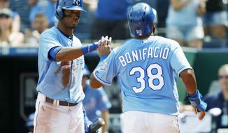 Kansas City Royals' Rosell Herrera (7) congratulates Jorge Bonifacio (38) after scoring in the third inning of a baseball game against the Baltimore Orioles at Kauffman Stadium in Kansas City, Mo., Sunday, Sept. 2, 2018. Bonifacio reached home plate from second on two errors by the Orioles. (AP Photo/Colin E. Braley)