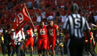 Maryland offensive lineman Ellis McKennie (68) walks with teammate Taivon Jacobs as he waves a flag in remembrance of offensive lineman Jordan McNair, who died after collapsing on a practice field during a spring practice, after an NCAA college football game against Texas, Saturday, Sept. 1, 2018, in Landover, Md. Maryland won 34-29. (AP Photo/Patrick Semansky) **FILE**
