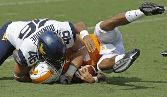 West Virginia's Reese Donahue (46) sacks Tennessee's Jarrett Guarantano (2) in the first half of an NCAA college football game in Charlotte, N.C., Saturday, Sept. 1, 2018. (AP Photo/Chuck Burton)