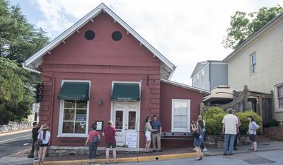 """Passersby gather to take photos in front of the Red Hen Restaurant, Saturday, June 23, 2018, in Lexington, Va. White House press secretary Sarah Huckabee Sanders said Saturday in a tweet that she was booted from the Virginia restaurant because she works for President Donald Trump. Sanders said she was told by the owner of The Red Hen that she had to """"leave because I work for @POTUS and I politely left."""" (AP Photo/Daniel Lin)"""