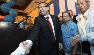 FILE - In this Sept. 9, 2014, file photo, Rhode Island Republican gubernatorial nominee Allan Fung shakes hands with a supporter as his mother, Tan Ping Fung, center, and father, Kwong Wen Fung, right, watch during a primary election night watch party in Warwick, R.I. Fung is seeking the Republican nomination in the Sept. 12, 2018 primary, to again run for governor. (AP Photo/Gretchen Ertl, File)