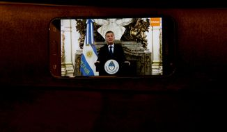 A journalist's phone, showing a pre-recorded video of Argentine President Mauricio Macri giving a message, lies on a chair at the Economy Ministry ahead of a press conference with Treasury Minister Nicolas Dujovne in Buenos Aires, Argentina, Monday, Sept. 3, 2018. Macri announced a withholding tax on exports and the elimination of several ministries amid economic turmoil that has sent the peso to record lows. (AP Photo/Natacha Pisarenko)