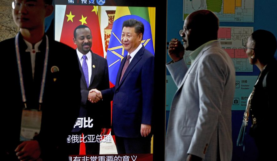 African delegates walk by a screen panel showing a footage of Chinese President Xi Jinping with Ethiopia's Prime Minister Abiy Ahmed ahead of the Forum on China-Africa Cooperation in Beijing, Monday, Sept. 3, 2018. African leaders will likely press their Chinese hosts at a conference this week to help narrow their trade deficits with Beijing by shifting more manufacturing to their continent, the chief executive of the biggest African bank said. (AP Photo/Andy Wong)